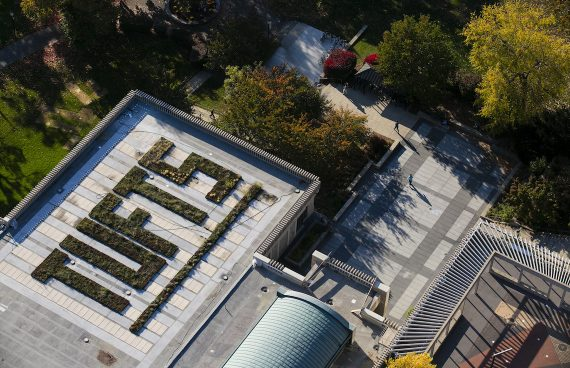 "birdseye view of a building at Tufts with a green roof, the greenery spells out ""TUFTS"""