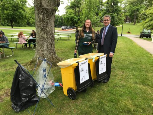 A woman and a man in smiling near compost bins at a zero waste event