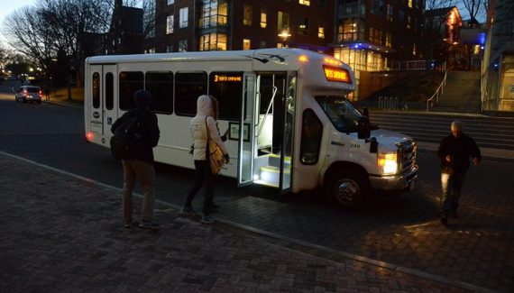 Students boarding a Tufts shuttle