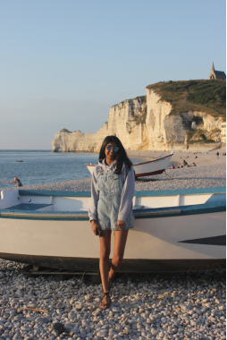 Girl standing in front of a boat on a beach with cliffs in the background