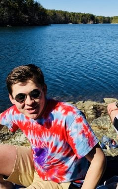 Picture of Mike, an eco-rep, by a body of water in a tie dye shirt and sunglasses