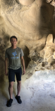 Boy smiling standing in a cave