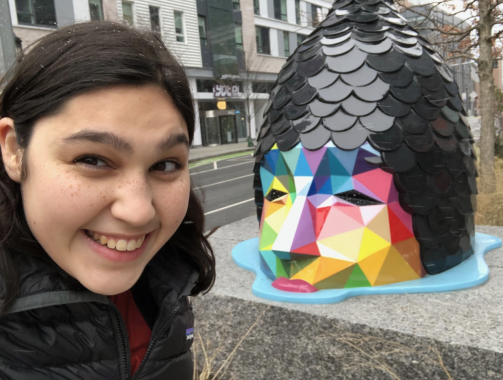 Close-up of a girl smiling with a multi-colored sculptural head in the background