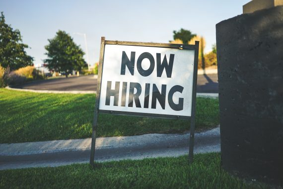 """""""Now Hiring"""" sign stuck into the grass"""